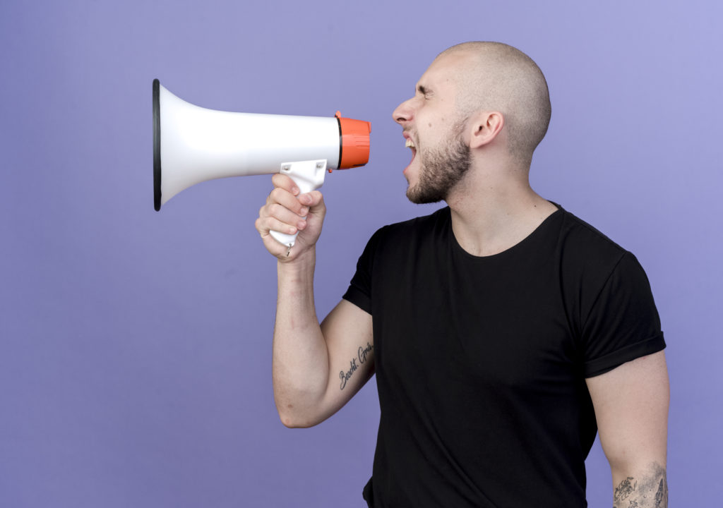 with closed eyes young sporty man speaks on loudspeaker isolated on purple background